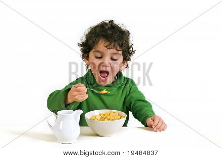young boy eating cornflakes isolated on white