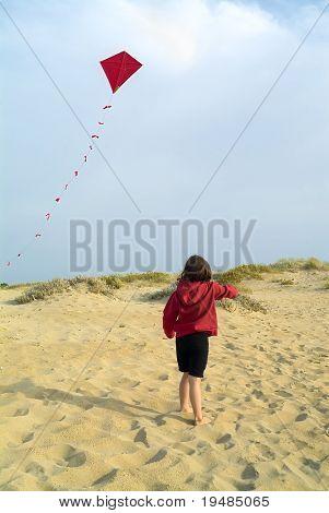 chica en la playa y un cometa rojo