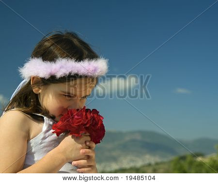 little girl smelling red roses against blue sky and a cloud