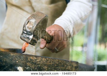 blacksmith working metal with hammer and anvil