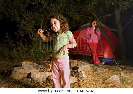 dos chicas en un campamento de comer melcocha