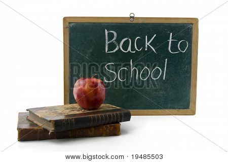 red apple on two old books in front of an old blackboard