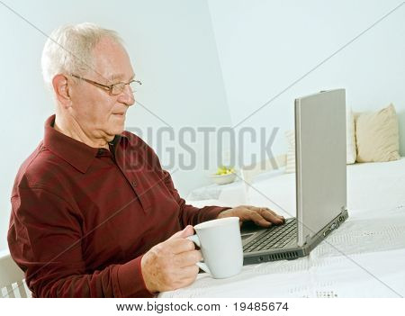senior man with laptop computer at home