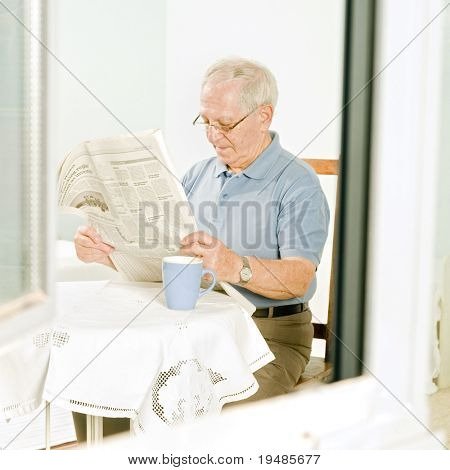 senior man reading a newspaper at home