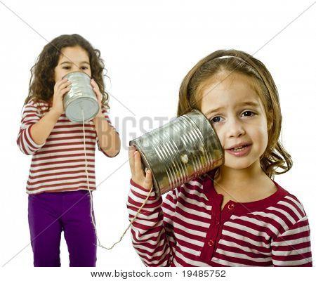 zwei Mädchen sprechen auf einem Blech Telefon, isolated on white
