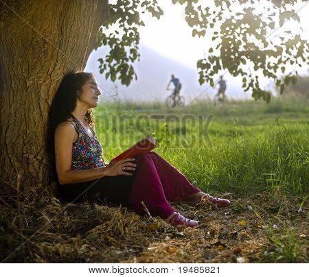 woman sitting under tree reading a book