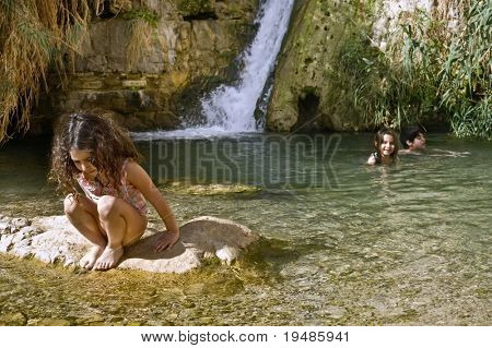 Three kids swimming in an oasis pool with waterfall
