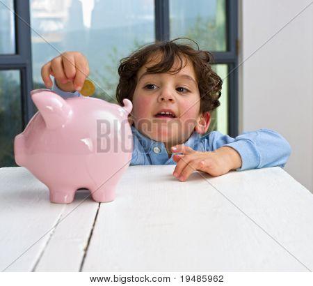 kleiner Junge hält ein Sparschwein