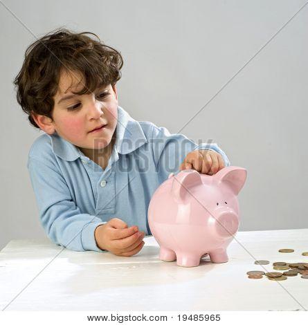 Junge einfügen eine Münze in ein Sparschwein