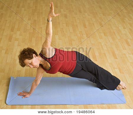senior woman doing bikram hot yoga in a gym