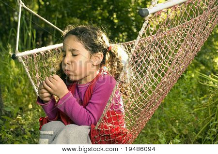 little girl sitting in a hammock blowing a dandelion