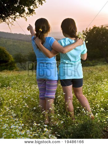 Two girls hugging in flowers in field at sunset