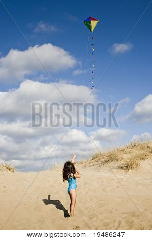 girl on beach playing with a colorful kite