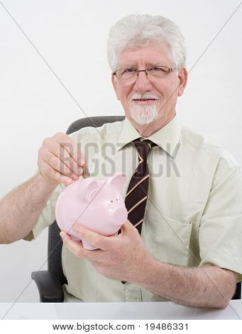 senior man holding a piggy bank over white