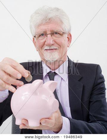 empresario Senior insertar una moneda en una alcancía sobre blanco