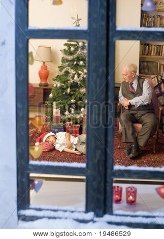 grandfather looking at his asleep grandchild under the Christmas tree.