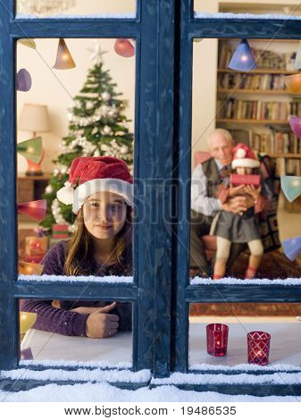 Child looking outside on Christmas eve.