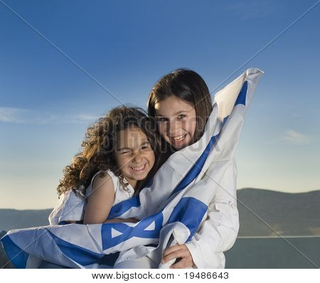 two girls holding hugging the Israeli flag