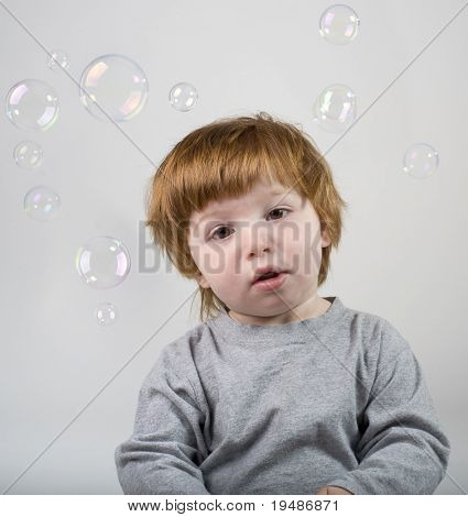 little redhead boy playing with soap bubbles