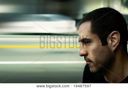 Dramatic edgy stylized cinematic portrait of a serious man with blurred city street and traffic in background