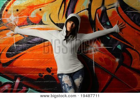 Hip young woman posing against graffiti wall