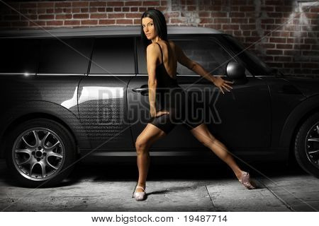 Hot female dance in alley against slick gray car and brick wall