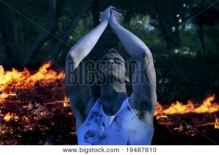 Dramatic twilight portrait of young emotional man with hands up praying in front of fire (slight night effect)