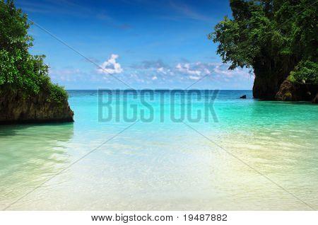 Hermosa cala apartada en el Caribe, con arenas blancas y aguas turquesas y azul cielo enmarcada por gr