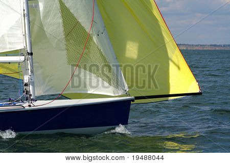 Forward to a victory under sails! The modern sports yacht rushes on the large speed. Yellow and white sails.