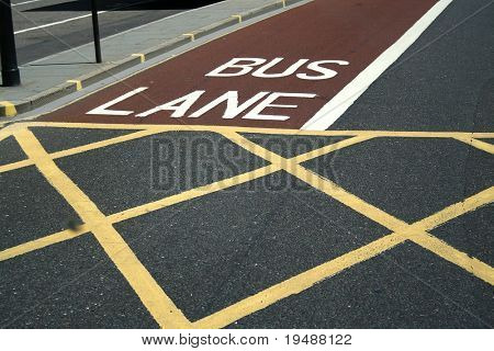 London. Road in  the city. Sectoring for buses and pedestrians. Red, white and yellow lines.
