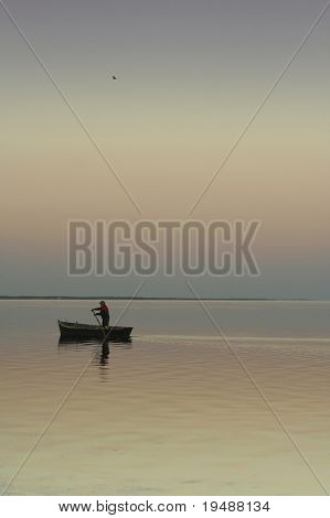 Lonely boat on silent water. Sunset. Beautiful reflection in water. One the man in a boat and one bird in the sky.