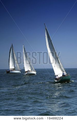 The large race began! Start of a sailing regatta. The sailing yachts compete in speed.