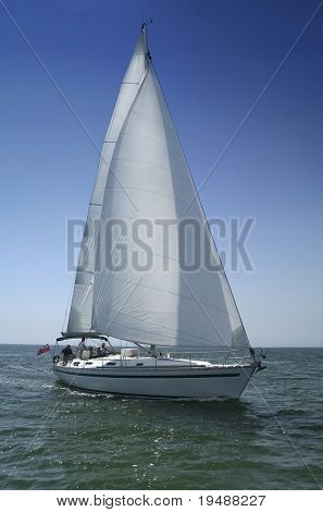 The large beautiful yacht with white sails on a background of the brightly light-blue clean sky and quiet sea.
