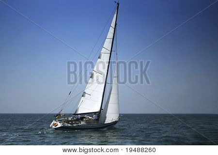 Yacht with white sails in dark blue open space. The good wind fills sails.