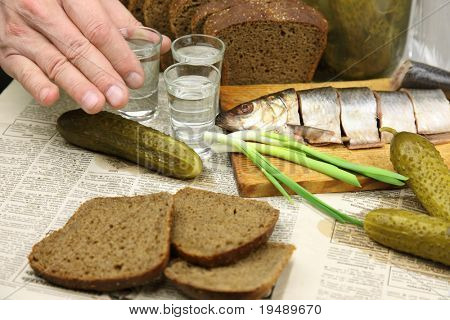 Vodka, herring, pickles, black bread on the tablecloth from the newspaper. Three hands are stemware, clink glasses, drink and a snack.