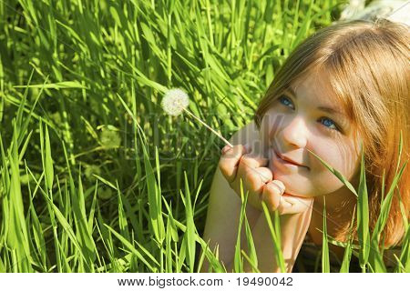 Girl with a Dandelion / against blue sky / freedom