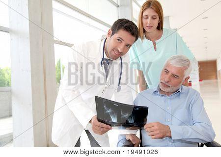 Equipe médica, verificando a radiografia com o paciente