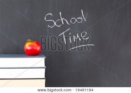 "Stack of books with a red apple and a blackboard with ""school time"" written on it"