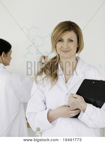 Two women in front of a white board in a lab