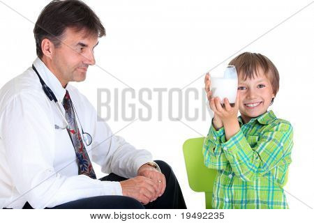 A doctor looking at a boy who is happily holding a glass of milk, on a white studio background.