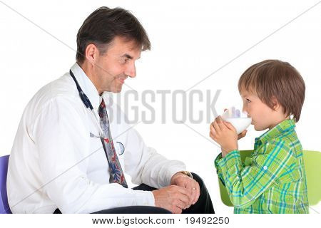 Side view of healthy young boy drinking glass of milk with smiling doctor, isolated on white background.