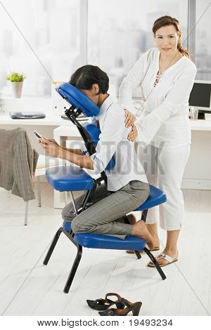 Businesswoman sitting on massage chair, getting back massage.?