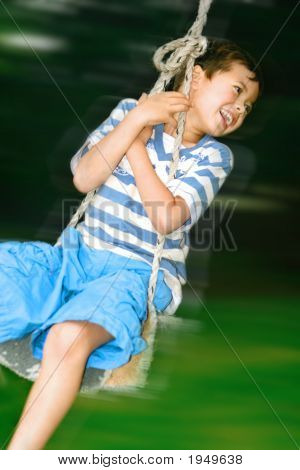 Young Boy Laughing As He Hangs In The Rope Swing In The Garden