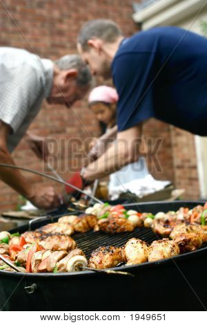 Family Having Barbecue Outdoor Helping Each Other