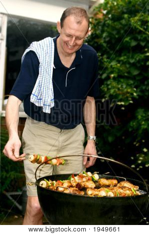 Man Tending To Sizzling Meat On Barbecue