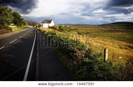 Road leading to chapel at wide field embedded in mystical ambiance, Isle of Skye, Scotland