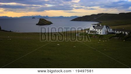 Scottish old house at sea shore with sheep on green field in evening ambiance, Isle of Skye, Scotland