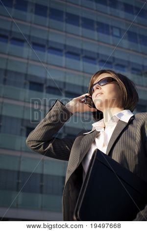 Young confident female professional talking on mobile phone and holding a briefcase, in front of office building