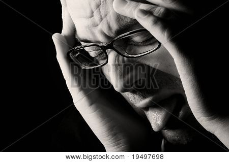 Close-up of young nauseated man, low key, black and white