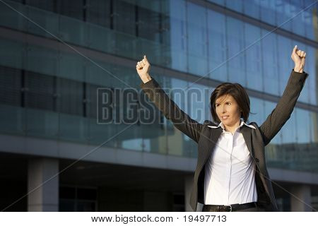 Young female professional lifting hands to celebrate business triumph, posing in front of blue glass facade of office building